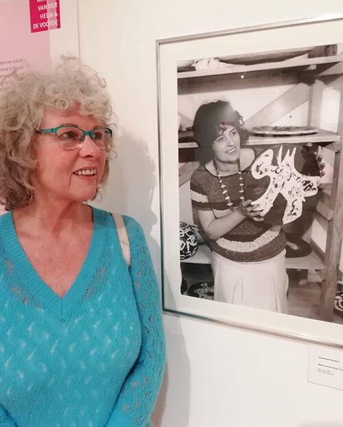Levina van de Bundt voor een foto van haar moeder Mieke van der Burgt met eigen werk